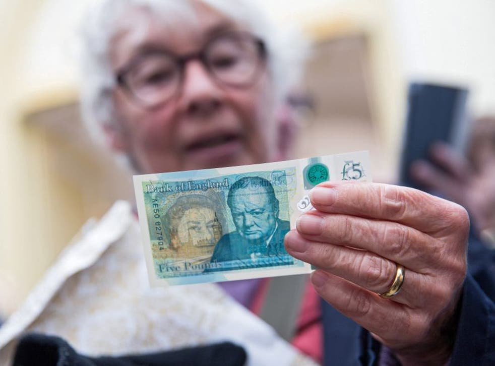 A woman surveys the new polymer £5 note