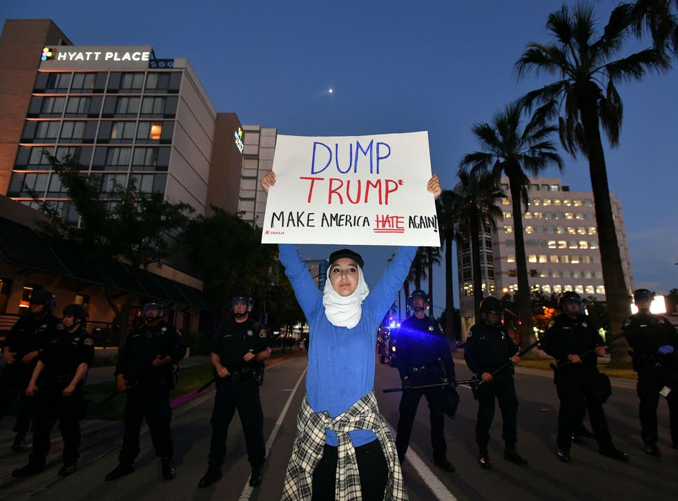 A protester holds up a placard outside a Donald Trump rally in San Jose, California on 2 June