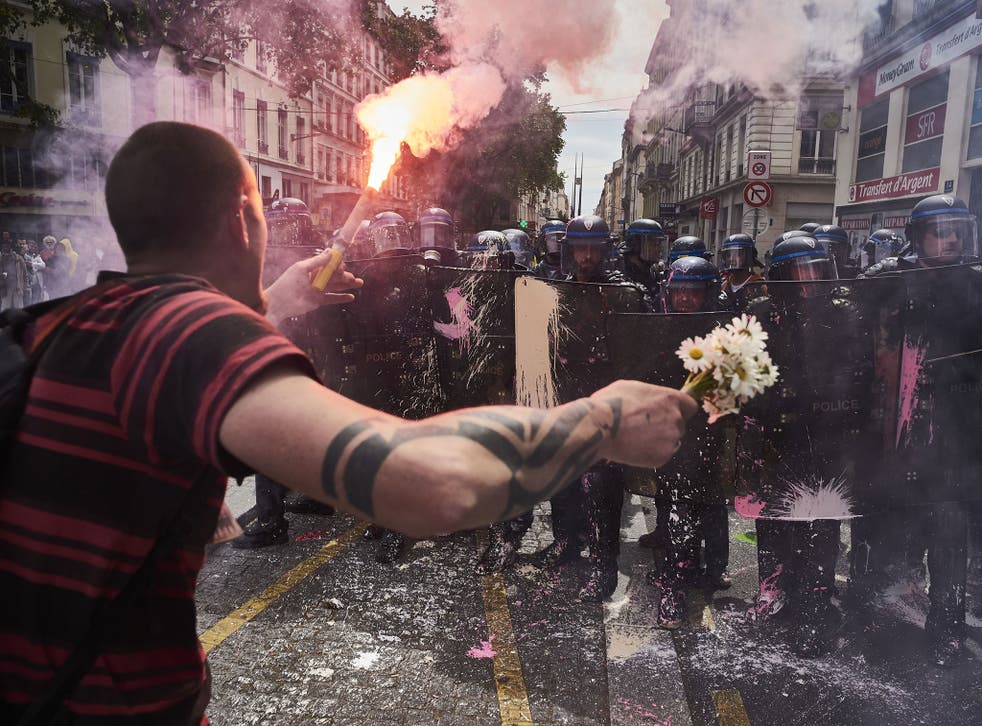 A man holds a bouquet of flowers and a torch as he faces riot police during a demonstration against the French government's planned labour reform on 26 May 2016 in Lyon, France