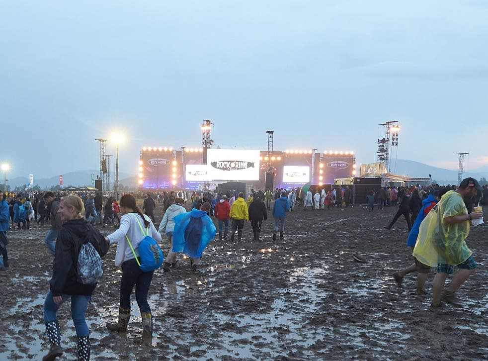 People walk on mud after the venue of the festival 'Rock am Ring' was hit by a storm in Mendig, Germany, 3 June 2016.