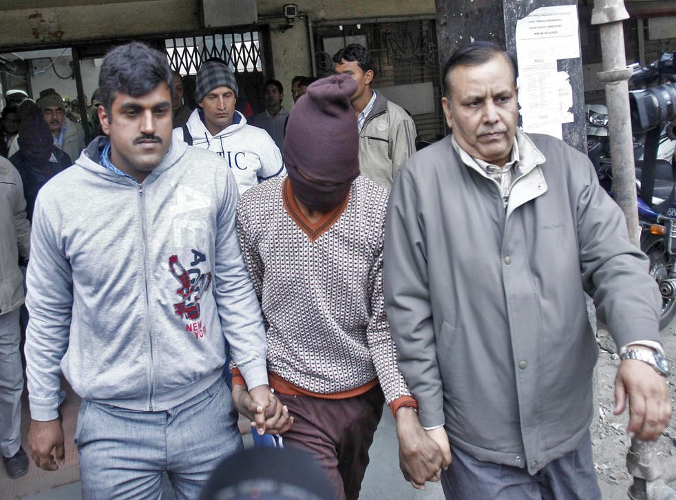 Plain-clothed police escort one of the men (face covered) accused of a gang rape outside a court in New Delhi