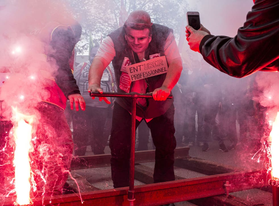 A French rail worker wearing a French Economy Minister Emmanuel Macron mask installs rails during a demonstration in front of the French employers' union MEDEF's branch in Lyon, central France, on Wednesday, June 1, 2016