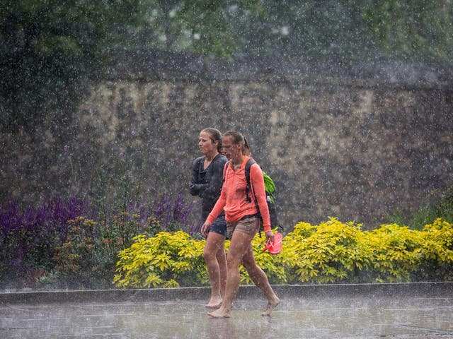 Two women walk barefoot through heavy rain in Westminster in London. The Met Office has issued flood alerts for parts of the south east of England as torrential rain hit parts of the country