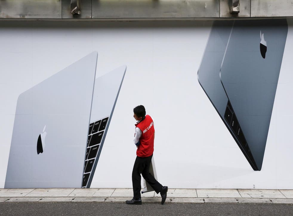 A staff member of Japanese electronic retailer Bic Camera walks past an advertising poster of Apple MacBook laptops in Tokyo, August 25, 2015