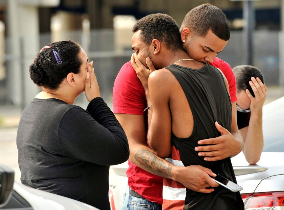 Orlando Police officers direct family members away from the scene of the shooting