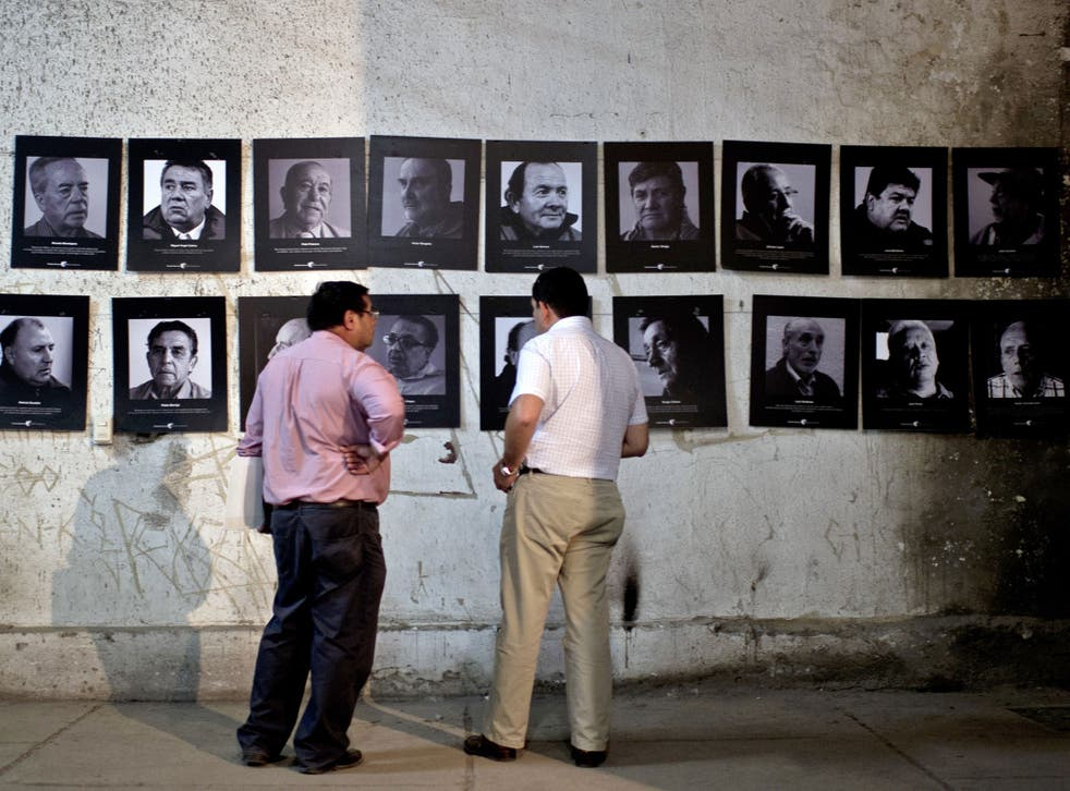 Members of the 'Former Political Prisoners of the National Stadium' stand next to pictures in a room at the National Stadium that served as a jail for prisoners during the killings