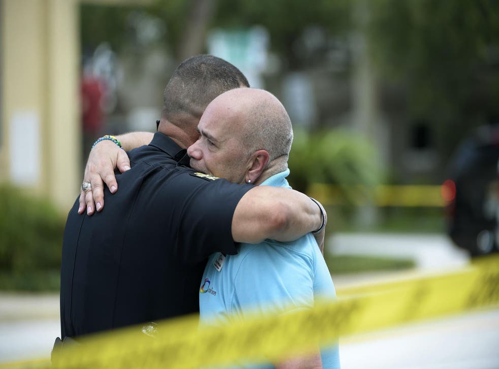 Police officer gives hug to Terry DeCarlo, executive director of LGBT Center of Central Florida