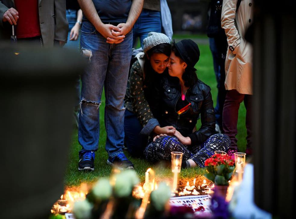 Mourners embrace during a candle-lit vigil, in memory of the victims of the gay nightclub mass shooting in Orlando, at St Anne's Church in the Soho