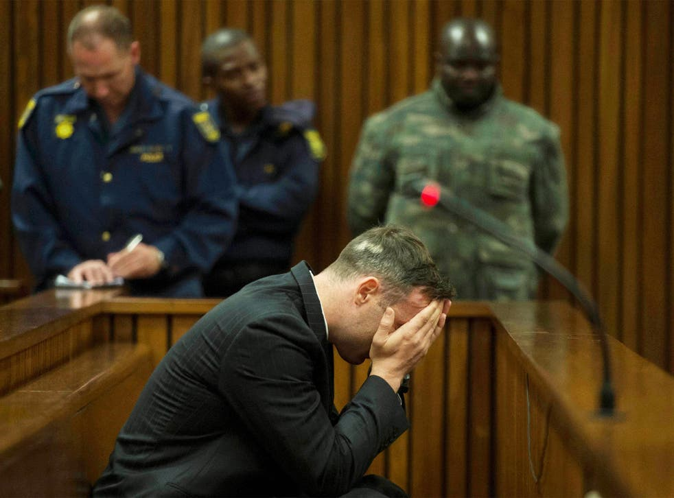 Oscar Pistorius covers his face as the father of his late girlfriend testifies at the Pretoria High Court yesterday
