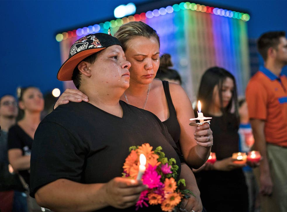 Nicole Edwards and her wife Kellie Edwards observe a moment of silence during a vigil outside the Dr. Phillips Center for the Performing Arts for the mass shooting victims at the Pulse nightclub June 13, 2016 in Orlando, Florida.