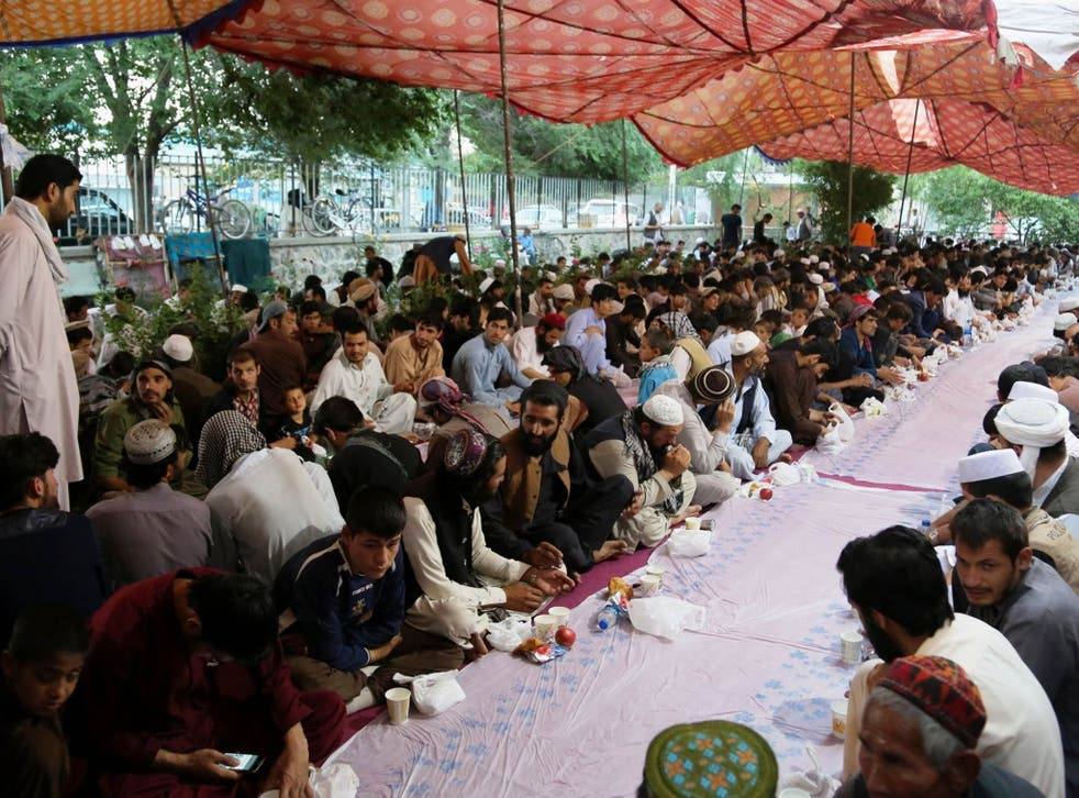 People prepare to break their fast during the Ramadan at a mosque in Kabul, 13 June 2016