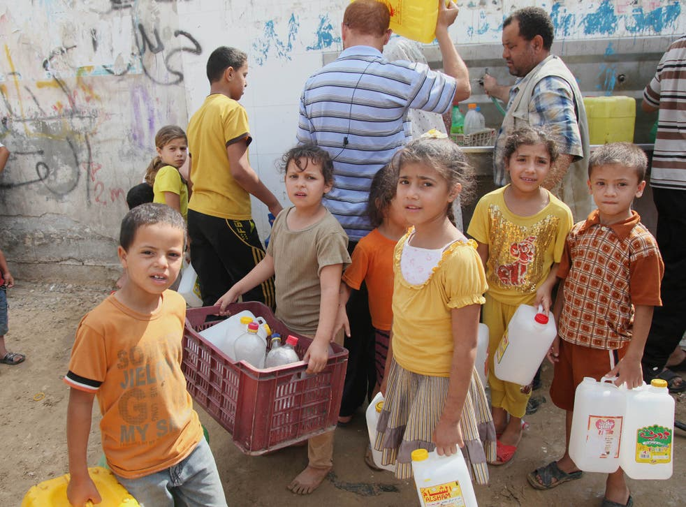Palestinian children fill bottles with water from a public tap in Khan Younis due to water shortages