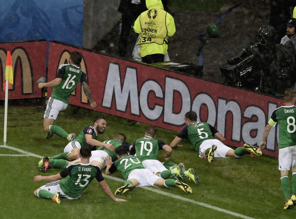 Gareth McAuley is mobbed by his team-mates after scoring the opener