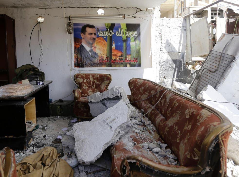 A poster of Syrian president Bashar al-Assad hangs in a Damascus apartment destroyed by car bomb <em>Louai Beshara/Getty</em>