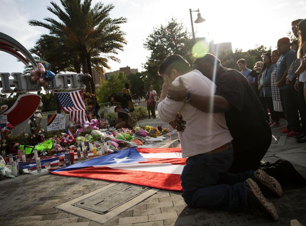 A mourner cries at a memorial near the Orlando Regional Medical Centre