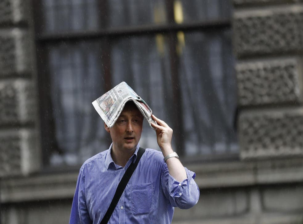 A man covers his head with a newspaper during heavy rain in London, Britain June 20, 2016