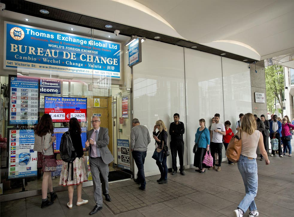 People queue for currency at a foreign exchange bureau in London yesterday
