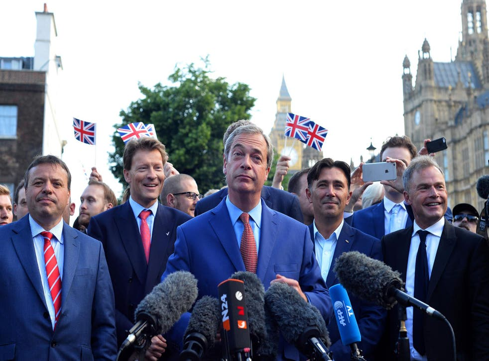 Nigel Farage (C) speaks during a news conference near the Houses of Parliament