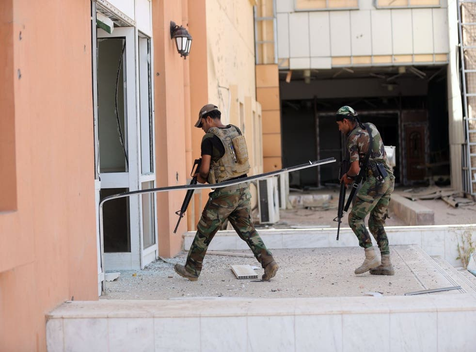 Two Iraqi soldiers enter the main hospital in Fallujah. Isis have controlled the since January 2014