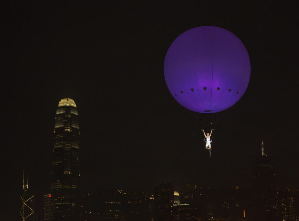 A dancer of London's the Dream Engine performs under the heliosphere, a massive helium balloon, with the backdrop of Hong Kong's skyline December 16, 2012