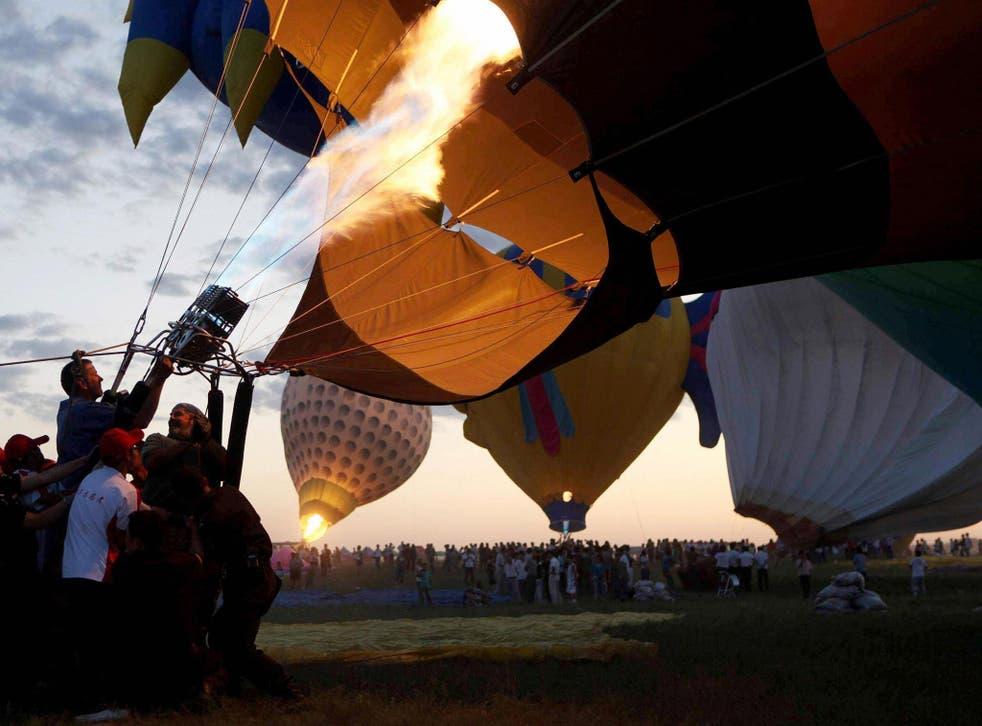 Contestants prepare their hot air balloons during an international hot air balloon festival in Baotou, north China
