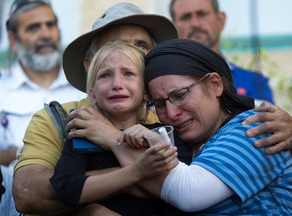 Hillel's mother, sister and father mourning at her funeral