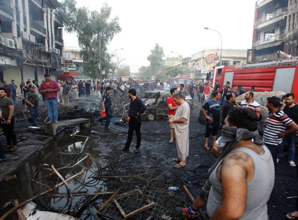 People gather at the site of a suicide car bomb in the Karada shopping area, in Baghdad, Iraq, 3 July, 2016