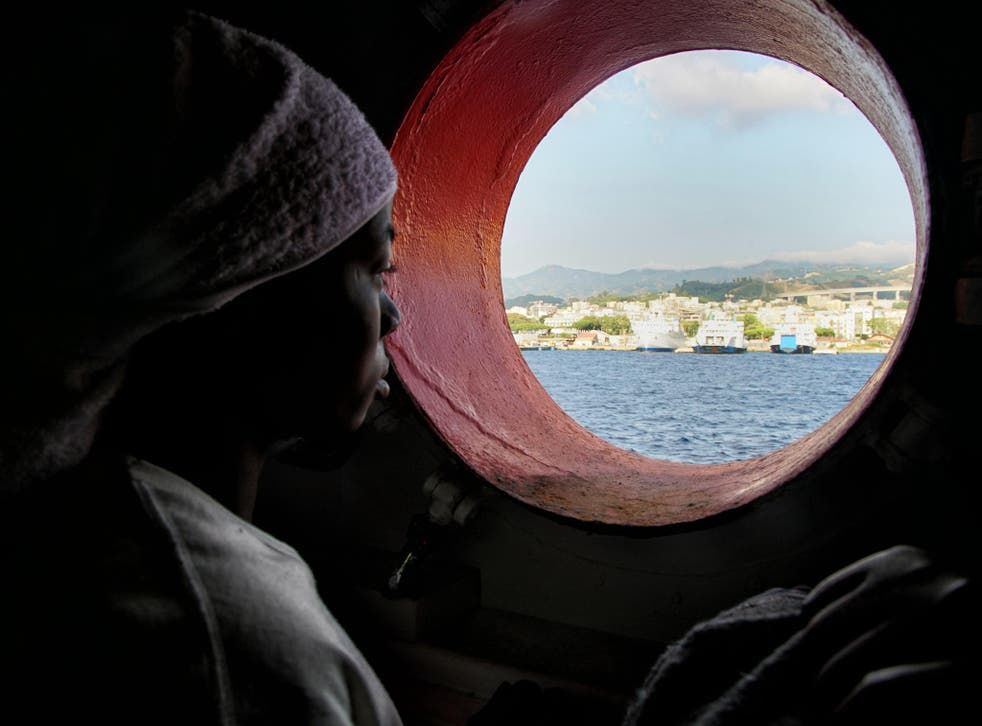 A woman looks out of the porthole from aboard the 'Aquarius' rescue vessel after arriving in Sicily, Italy, on Sunday June 25, 2016.  A group of more than 650 migrants arrived at port in Messina, Sicily, after being rescued from the Mediterranean Sea in June 2016