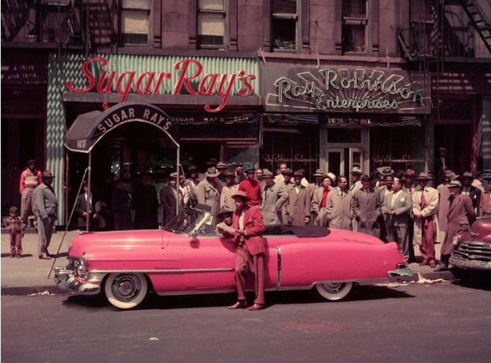 Sugar Ray Robinson enjoys the trappings of his success, stood next to his pink Cadillac and outside his Harlem club