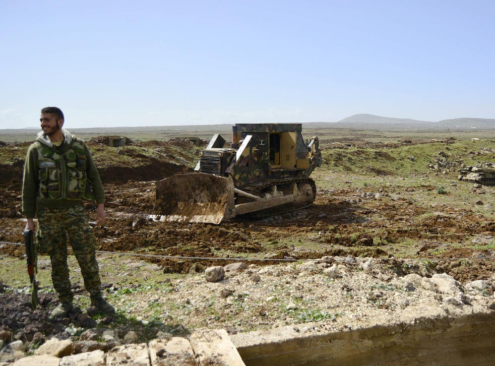 A member of the Syrian government forces stands infront of a bulldozer, north of the southern Syrian city of Deraa