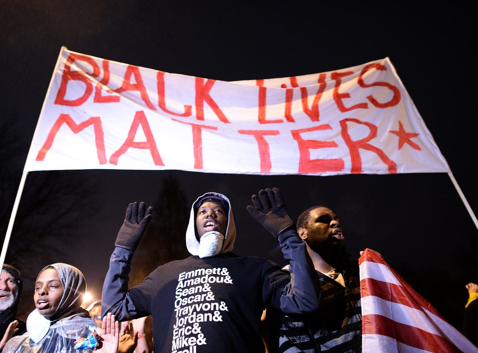 Demonstrators have their 'hands up' at a march protesting the death of 18-year-old Michael Brown in 2014