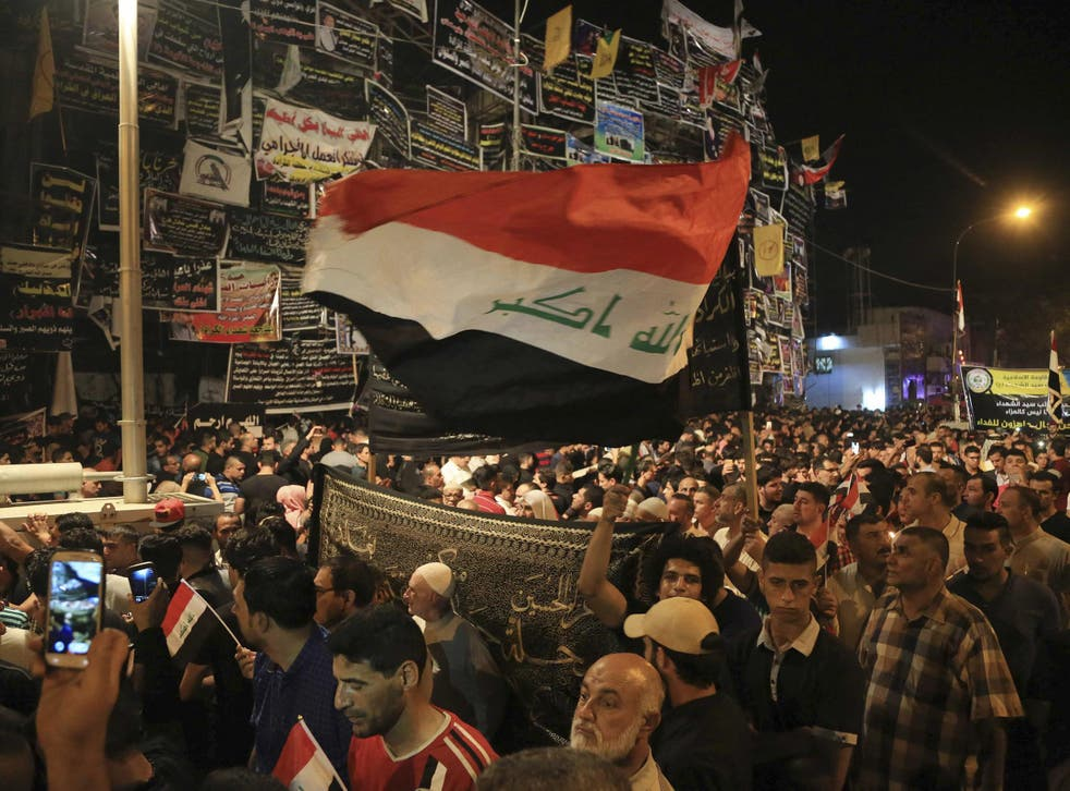 People gather to pay their respects to those killed in a bombing in Baghdad, which Isis said it was responsible for