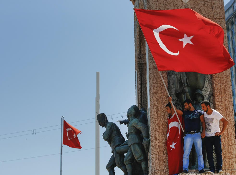 Anti-coup protesters wave a Turkish flag on top of the monument in Taksim square, Istanbul,