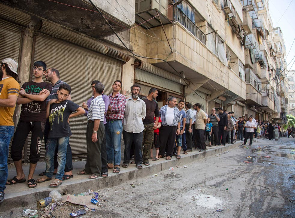 Syrians queue up to buy bread in a rebel held area of Aleppo on July 12, 2016.