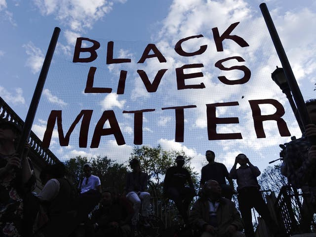 Protesters hold up a Black Lives Matter banner
