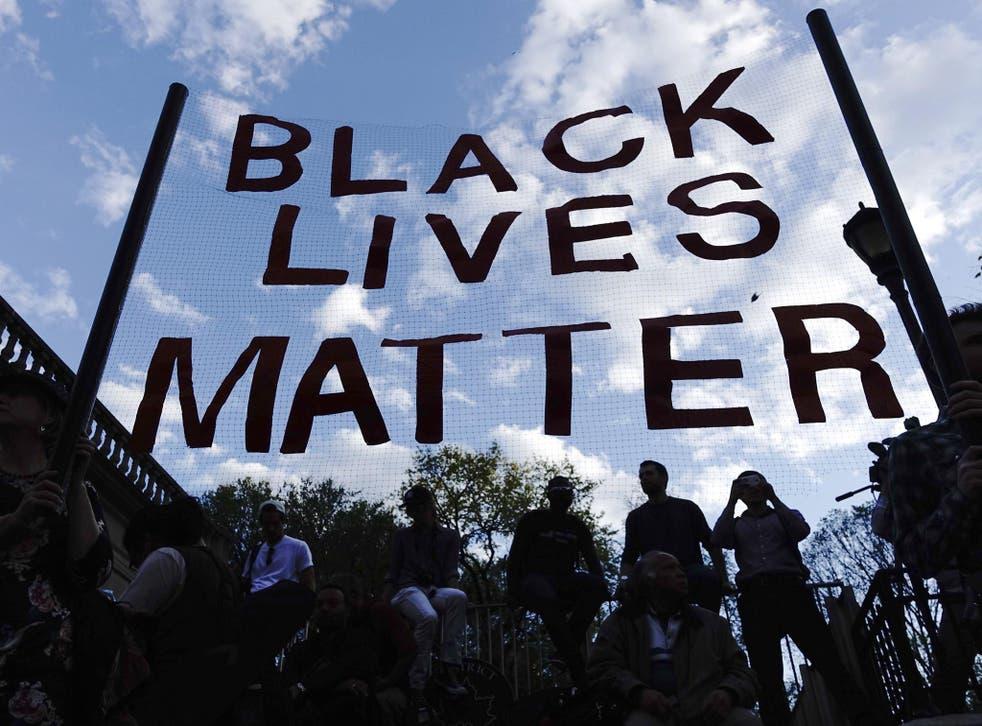 Protesters hold up a Black Lives Matter banner