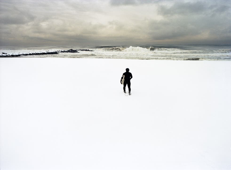 Kui, February Swell, 2005. A New York surfer rushes across a snowed covered beach to surf a cresting wave
