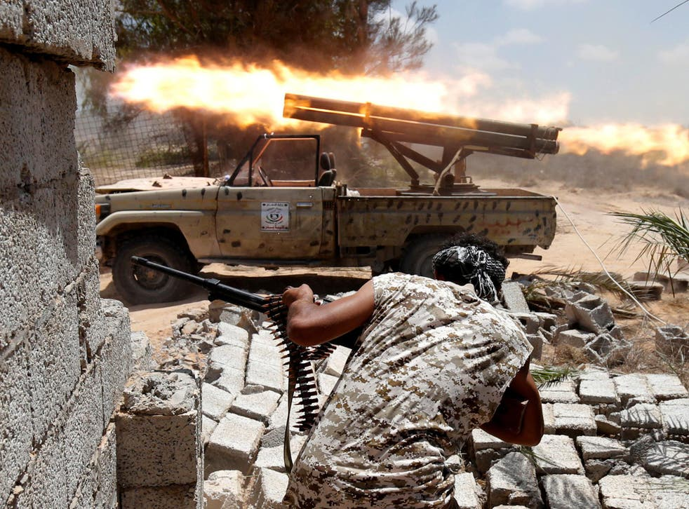 Libyan forces allied with the U.N.-backed government fire weapons during a battle with IS fighters in Sirte, Libya