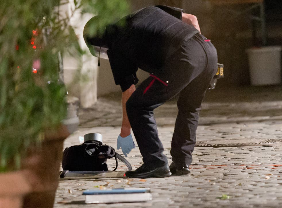 A police officer inspects a backpack used to carry an explosive device at the scene of the attack in Ansbach