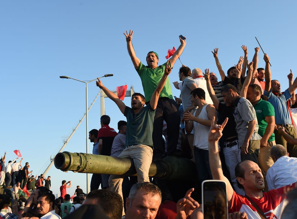 Civilians climb onto tanks after taking over military rebels' position on the Bosphorus bridge in Istanbul