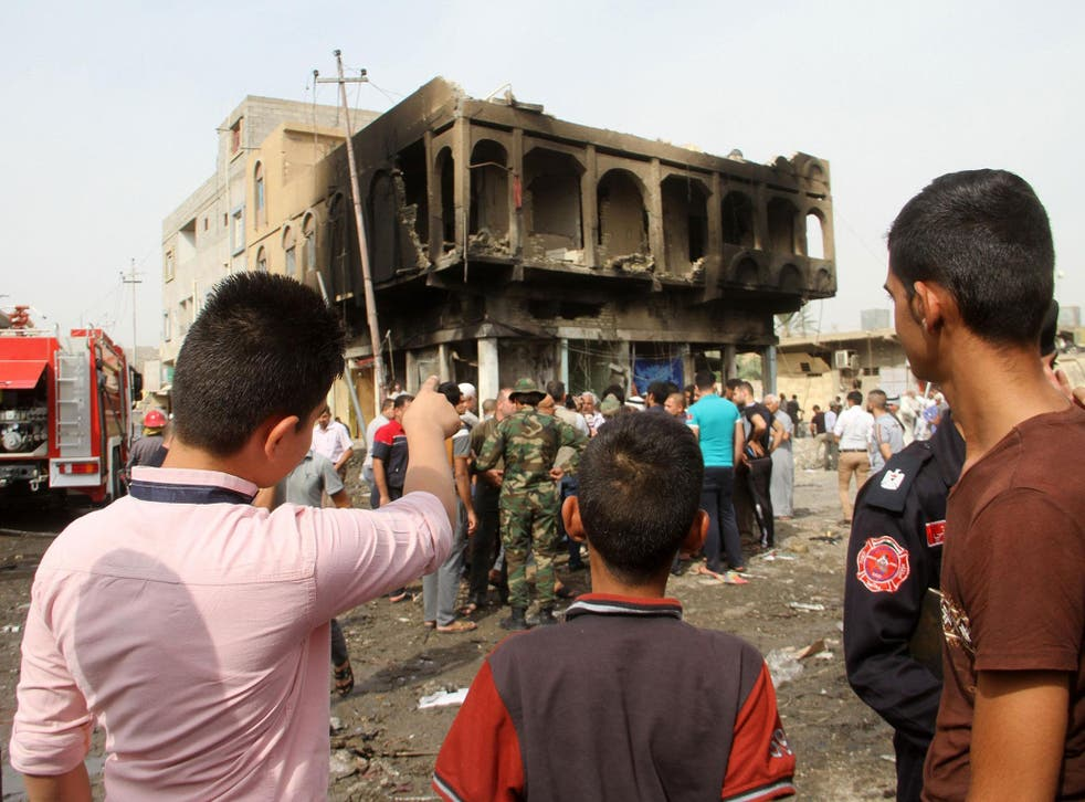 Iraqis look at a damaged building on October 6, 2015, a day after a blast in a market area of Khalis, around 55 kilometres from the capital Baghdad