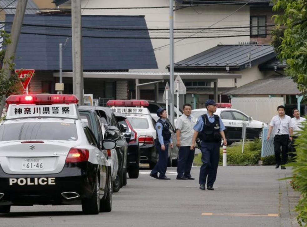 Japanese police officers check around a residential care facility (part of the facility tower is seen in rear) for disabled people in Sagamihara, Kanagawa Prefecture, about 60km west of Tokyo, Japan, 26 July, 2016