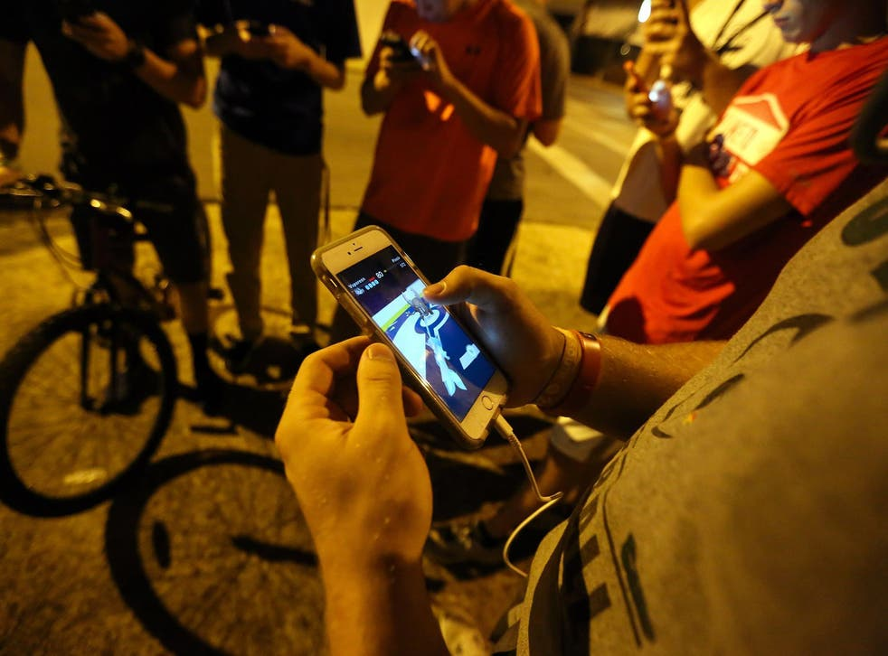 """A group of teenagers play """"Pokemon Go"""""""