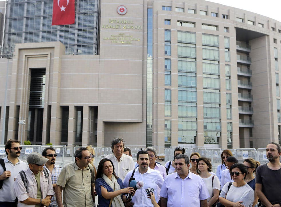 Journalists gather outside a court building to support their colleague Bulent Mumay, who was detained on Tuesday