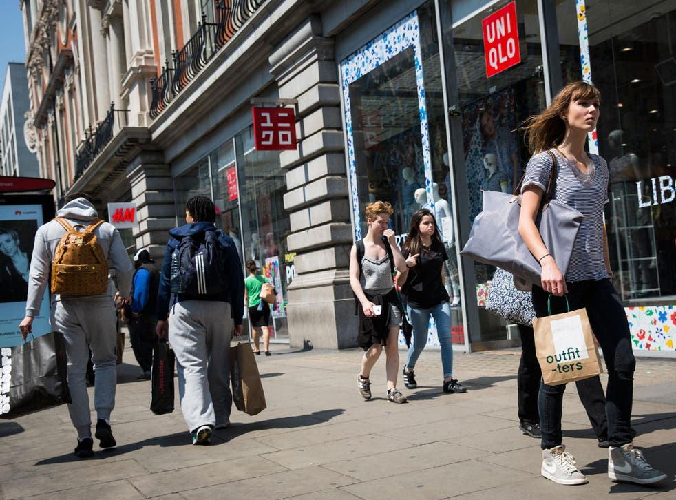 Shoppers carry bags with purchases on Oxford Street during the sales in June
