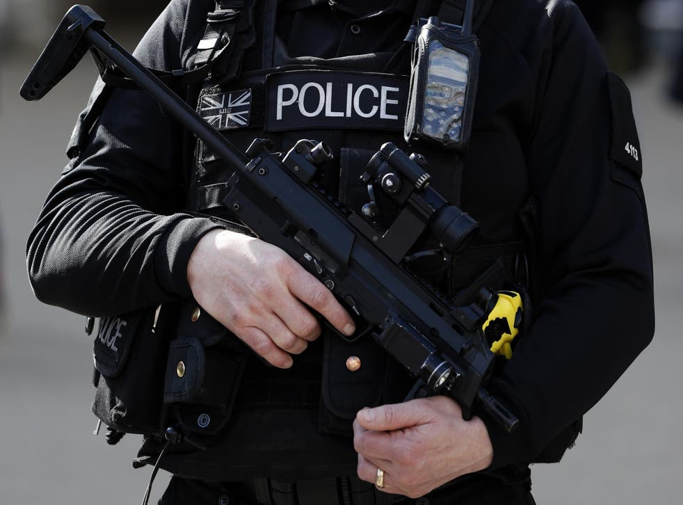 An armed British police officer holds his weapon as he stands on duty in central London in March 2016