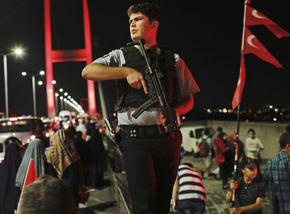 A Turkish police officer patrols as pro-government supporters, gather on Istanbul's iconic Bosporus Bridge, Thursday, July 21, 2016.
