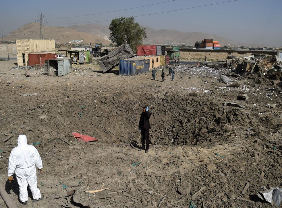 Afghan security personnel stand alert at the site after a powerful truck bomb targeting a hotel used by foreign contractors exploded on the outskirts of Kabul on August 1, 2016