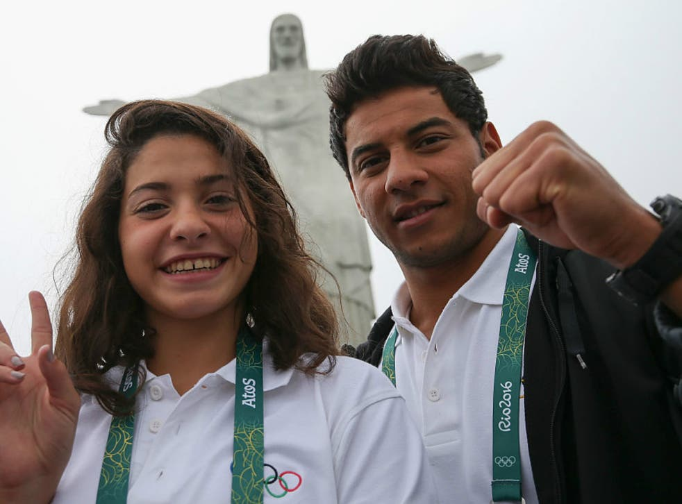 Olympic refugee team swimmers Yusra Mardini (L) and Rami Anis pose for a photo in front of the Christ the Redeemer statue on July 30, 2016 in Rio de Janeiro, Brazil.