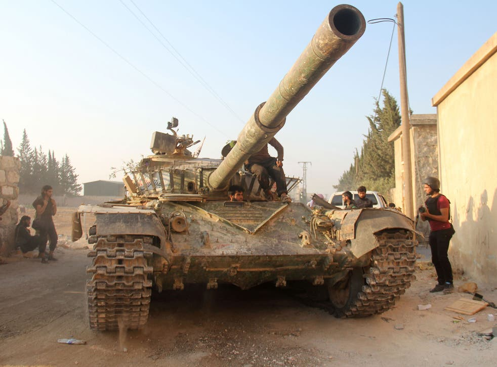 Fighters from the former Al-Nusra Front -- renamed Jabhat Fateh al-Sham after breaking from Al-Qaeda -- drive a tank as they seized key positions south of Aleppo in August 6, 2016 in